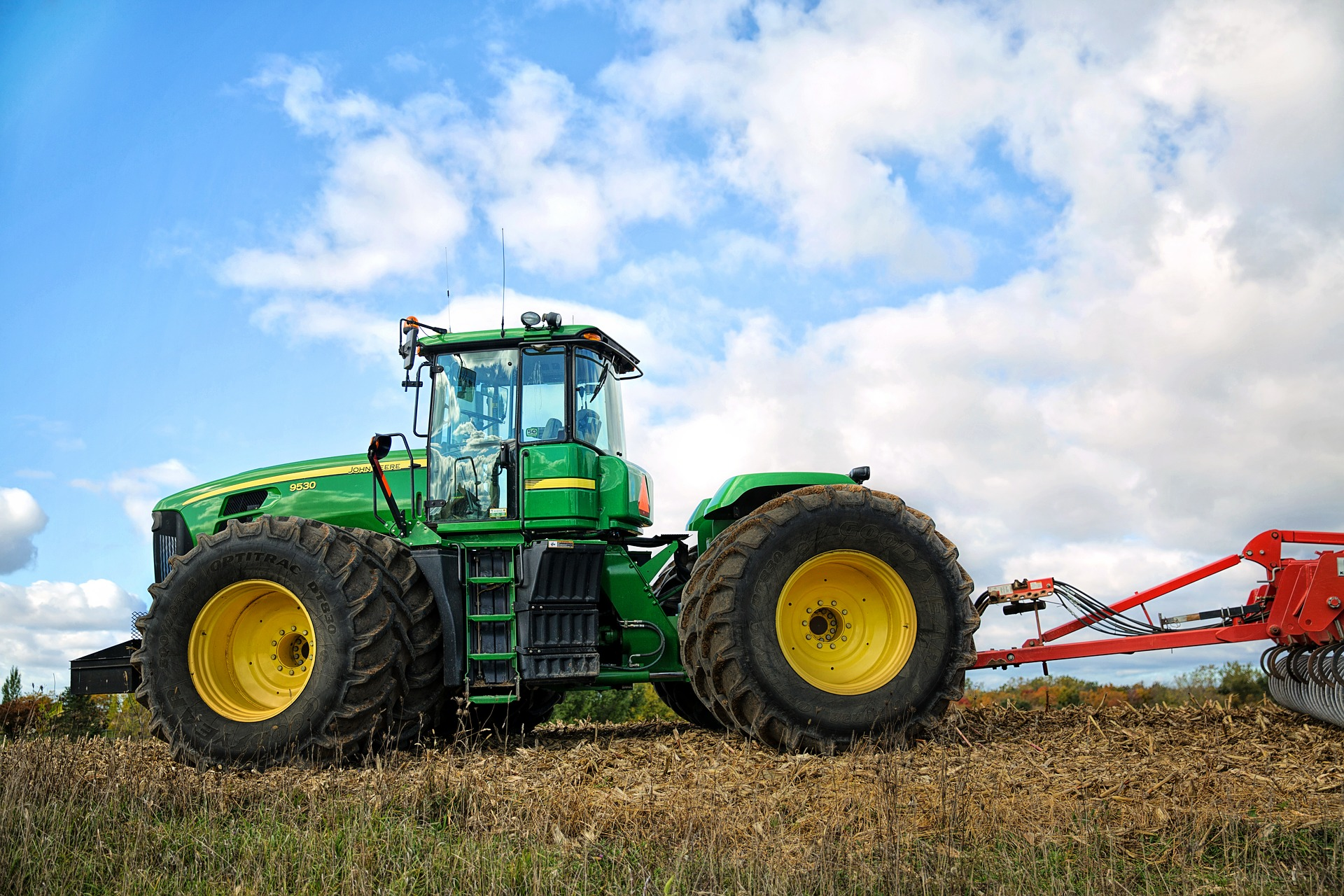 green tractor hauling red farm equipment