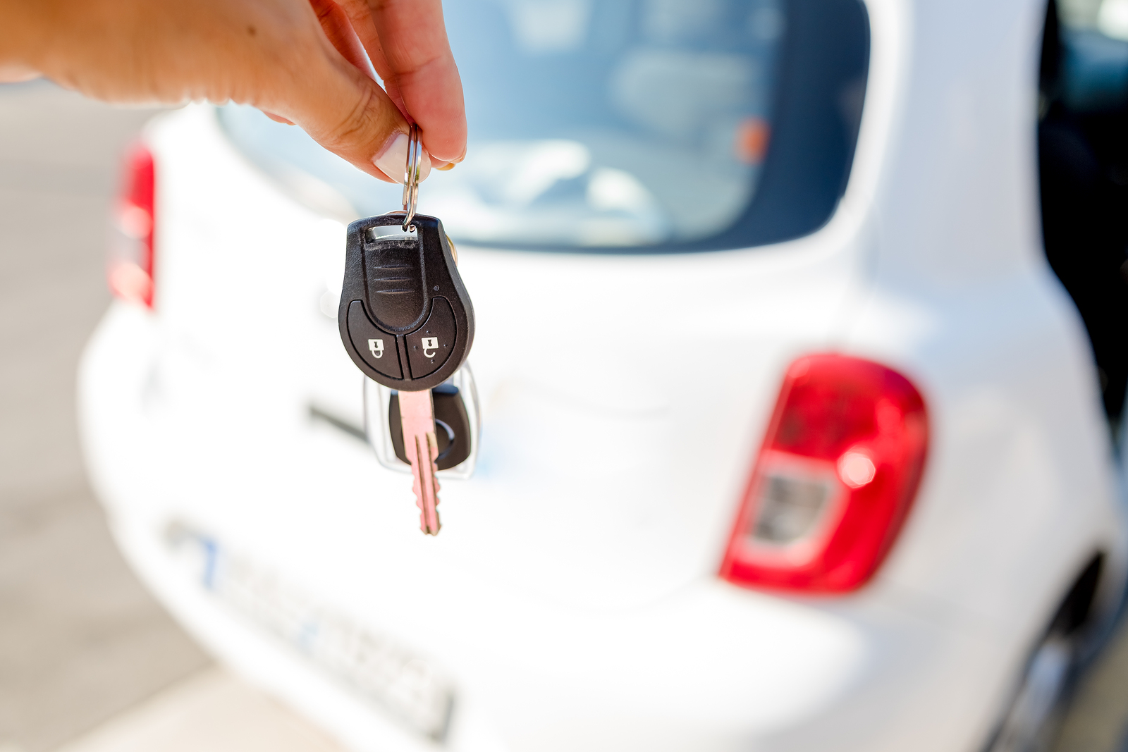 Woman with white painted fingernails giving car keys for white vehicle