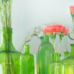 green glassware with some pink flowers