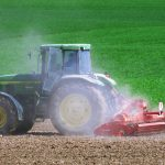 farm equipment driving across field of dirt with green grass in the background